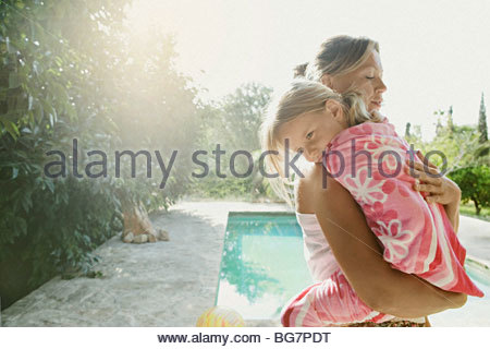 Mother carrying daughter wrapped in towel poolside - Stock Photo