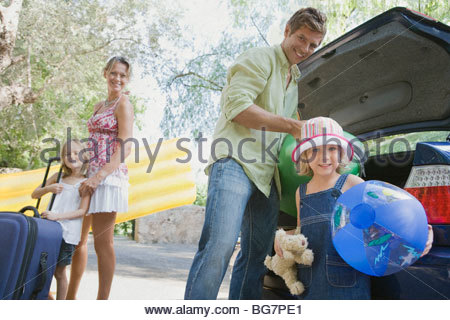 Family packing car with suitcases and beach toys - Stock Photo