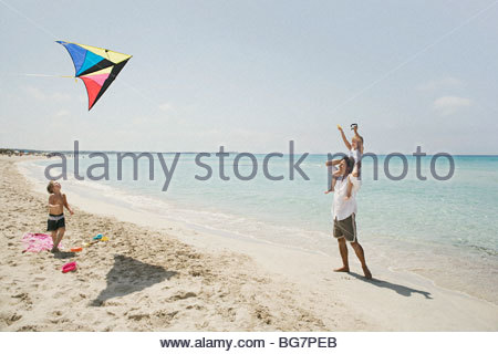 Family flying kite on beach - Stock Photo