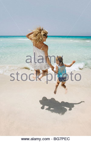 Mother and daughter jumping on beach - Stock Photo