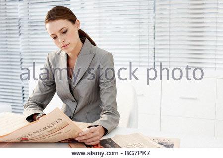 Businesswoman reading newspaper - Stock Photo