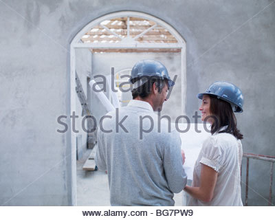 Couple holding blueprints in house under construction - Stock Photo