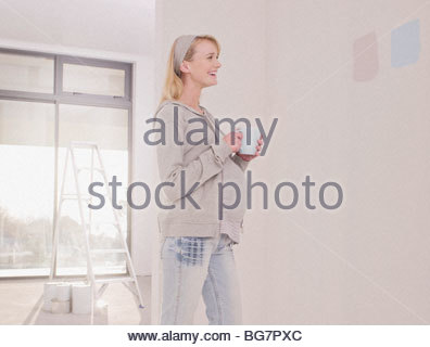 Pregnant woman looking at paint samples on nursery wall - Stock Photo
