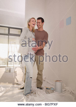 Pregnant woman and man painting nursery - Stock Photo