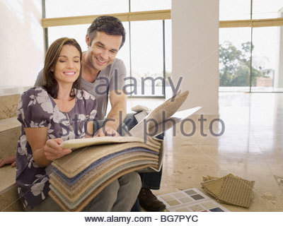 Couple looking at carpet samples in empty house - Stock Photo