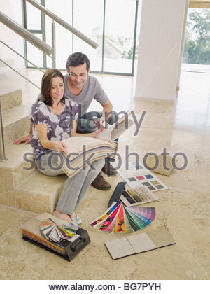Couple looking at carpet samples on staircase in empty house - Stock Photo