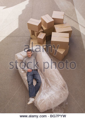 Man sleeping on sofa wrapped in plastic - Stock Photo