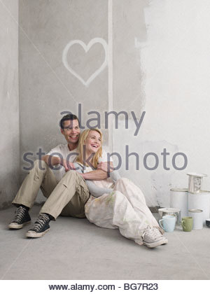 Couple sitting under painted heart on wall - Stock Photo