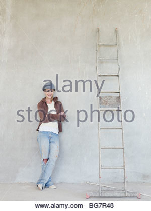Woman wearing hard-hat and leaning against wall with ladder - Stock Photo