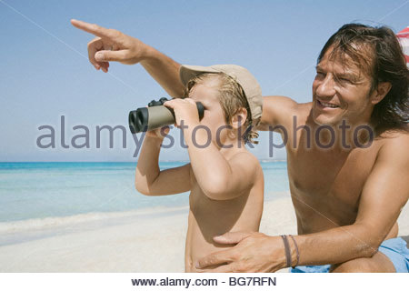 Father pointing and son looking through binoculars on beach - Stock Photo