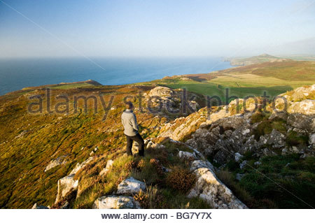 Walker looking North East from the summit of Carn Llidi, Pembrokeshire, South Wales. - Stock Photo