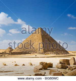 A man on camelback is dwarfed by the Pyramid of Menkaure, Giza Pyramids, Cairo, Egypt. - Stock Photo