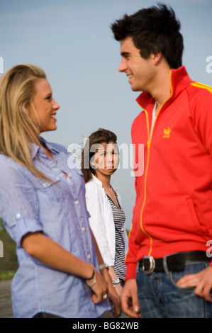 teenage couple holding hands with a jealous girl looking on - Stock Photo