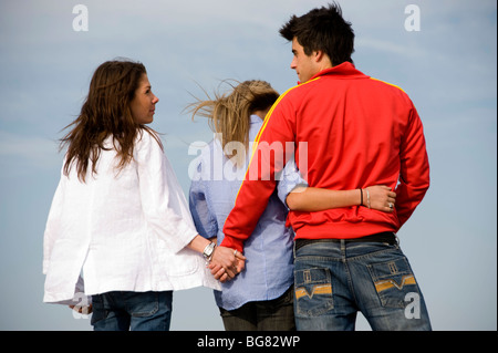 teenage couple cuddling each other with the boy holding hands with another girl - Stock Photo