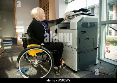 A young disabled woman in a wheelchair working using a photocopier machine in a modern office, UK - Stock Photo