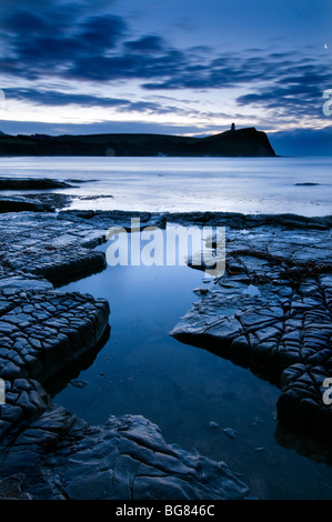 Dawn at Kimmeridge Bay, Dorset with Clavell Tower in the distance - Stock Photo