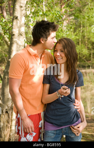 teenage couple outdoors in a wood with the boy kissing the girls head - Stock Photo