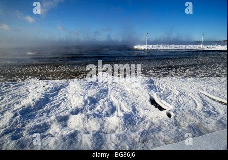 Blowing snow and steam from the still unfrozen Lake Mendota at Warner Park Beach and boat launch in Madison, Wisconsin - Stock Photo