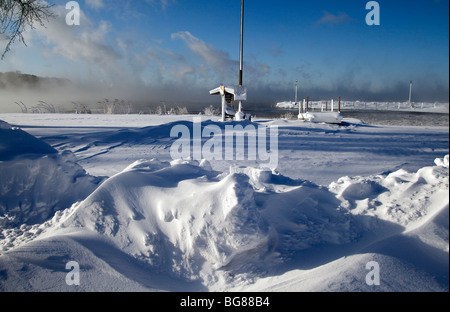 Blowing snow and steam from the still unfrozen Lake Mendota at Warner Park Beach and boat launch in Madison, Wisconsin. - Stock Photo