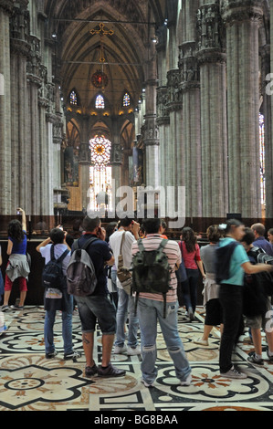 Nave and interior of il Duomo di Milano catholic cathedral Milan Italy with tourists and visitors inside - Stock Photo