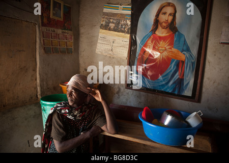 An HIV positive woman peers out the door of her home in Mererani, Tanzania. - Stock Photo