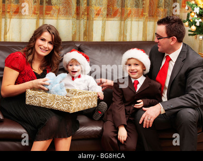 Family opening present on Christmas night on the sofa posing to the camera smiling and laughing - Stock Photo