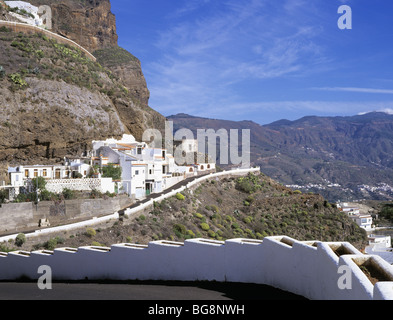 Artenara, Gran Canaria, Canary Isles, Spain. Winding road and cave houses built into the rock in highest village - Stock Photo