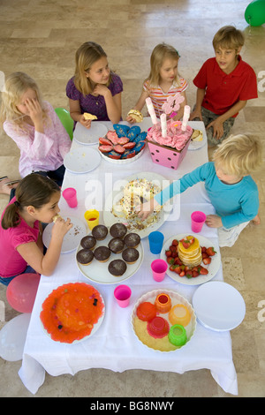 Small Children's - kids around table with sweets and cakes - Stock Photo