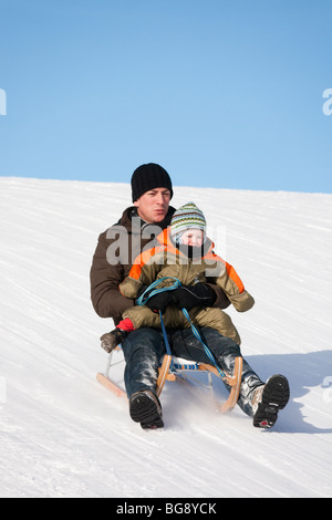 Man with a small child on his knee tobogganing down hill on a snow slope. Austria Europe. - Stock Photo