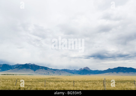 Mountain, agricultural land, and sky as seen from highway 287 in Madison County, Montana, USA. - Stock Photo
