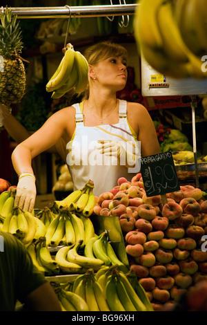 Central market stall woman selling Mercado de Boqueria on Las Ramblas Barcelona Spain - Stock Photo