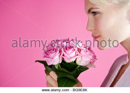 A Young Woman Smelling A Bunch Of Pink Roses - Stock Photo