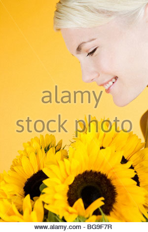 A Young Woman Looking At A Bunch Of Sunflowers - Stock Photo