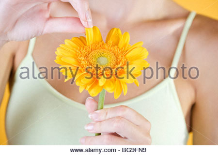 A Young Woman Plucking The Petals From An Orange Flower - Stock Photo