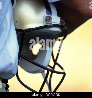Close up of an American football player holding his helmet - Stock Photo