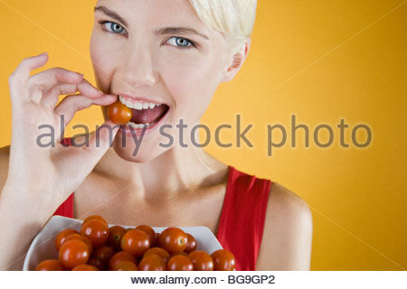 A Young Woman Eating A Cherry Tomato From A Bowl - Stock Photo
