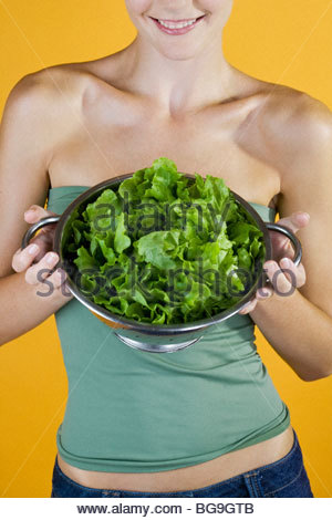 A Young Woman Holding A Colander Full Of Lettuce - Stock Photo