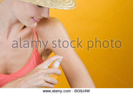 A Young Woman Spraying Suntan Lotion On Her Arm - Stock Photo