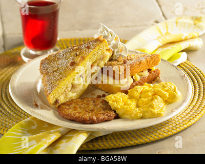 Banana stuffed French toast with scrambled eggs and sausage patty - Stock Photo