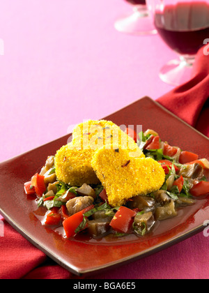 Baked cornmeal crusted tofu hearts with eggplant and red pepper stew - Stock Photo