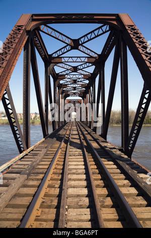 Railroad tracks through a steel railroad bridge, Laval, Quebec, Canada - Stock Photo