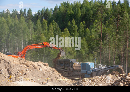 Digger loading sand and stones to the crusher / separator machine in a gravel pit , Finland - Stock Photo