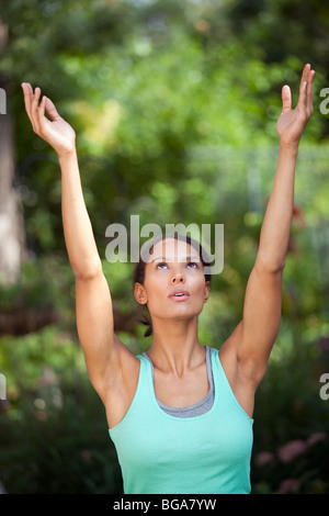 Young woman with arms raised in outdoor setting. Vertically framed shot. - Stock Photo