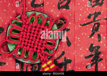 Red lucky knot in a ceramic plate,the background is calligraphy blessing words. - Stock Photo