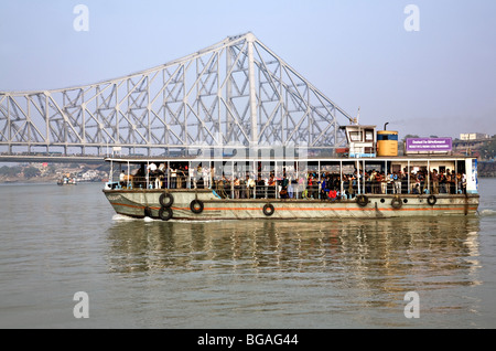 Shuttle ferry crossing the Hooghly river. On the background the Howrah bridge. Calcutta (Kolkata). India - Stock Photo