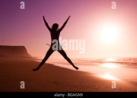 Picture of a female silhouette of a young girl jumping on the beach at the sunset - Stock Photo