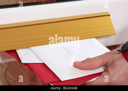 postmans hand pushing letters and cards into the letterbox of a house in the uk - Stock Photo