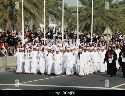Flag-waving Qatari children lead the official parade for national day in Doha, Qatar, December 2009 - Stock Photo