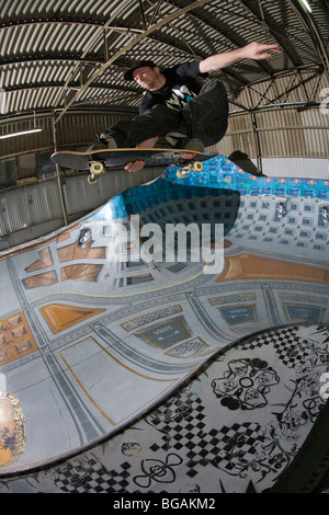 Skateboarder Danny Wainwright does an ollie in an indoor warehouse - Stock Photo