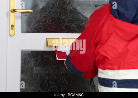 postman posting letters and cards through the letterbox of a house in the uk - Stock Photo